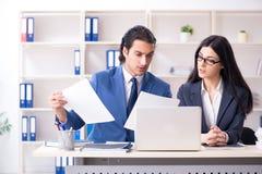 Os dois empregados que trabalham no escrit?rio fotos de stock