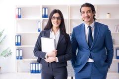 Os dois empregados que trabalham no escrit?rio imagens de stock