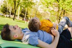 Os dois irmãos alegres encontram-se na grama no parque e no jogo em jogos engraçados fotos de stock