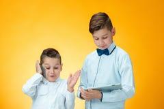 Os dois meninos que usam o portátil no fundo alaranjado Imagens de Stock Royalty Free