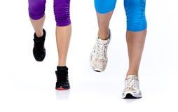 Os dois pés da mulher que funcionam em um fundo branco Imagens de Stock