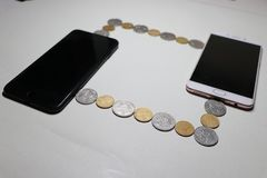 Os dois telefones celulares são conectados por um fio compostos das moedas fotos de stock royalty free