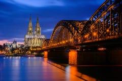 Os DOM da catedral na água de Colônia Alemanha na hora azul imagens de stock royalty free