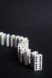 Os dominós alinham e o fundo do preto do conceito do negócio do líder Fotografia de Stock Royalty Free