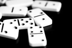 Os dominós são dispersados em uma superfície escura Rebecca 36 fotos de stock royalty free