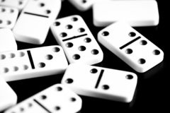 Os dominós são dispersados em uma superfície escura Rebecca 36 imagem de stock