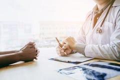 Os doutores e os pacientes sentam-se e falam-se Na tabela perto da janela imagem de stock