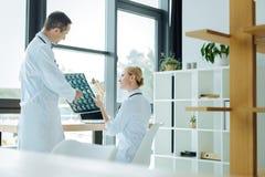 Os doutores espertos positivos que discutem um raio de X fazem a varredura Foto de Stock Royalty Free