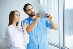 Os doutores masculinos e fêmeas trabalham junto no hospital Fotos de Stock Royalty Free