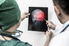 Os doutores que olham o filme de raio X do ` paciente s dirigem foto de stock