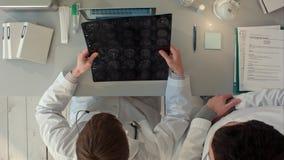 Os doutores team tendo uma discussão e reveem uma ressonância magnética Vista superior imagens de stock royalty free