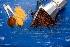 Os eans de Arabika no potenciômetro do moka, no açúcar mascavado e no café à terra no azul de madeira pintaram a tabela Fotografia de Stock