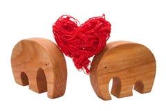 Os elefantes decorativos mantêm o coração junto imagem de stock