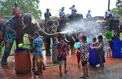 Os elefantes jogam a batalha da água com as crianças durante Songkran Imagens de Stock