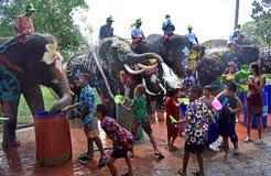 Os elefantes jogam a batalha da água com as crianças durante Songkran imagens de stock royalty free