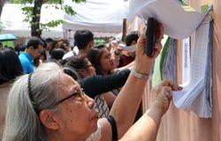 Os eleitores tailandeses verificam sua lista de nomes durante o avanço votaram fotos de stock