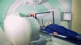 Os elementos de um acelerador linear estão revolvendo em torno de um paciente video estoque