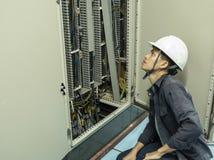 Os eletricistas estão verificando os painéis de controle elétricos em plantas industriais imagens de stock