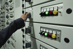 Os eletricistas est?o verificando os pain?is de controle el?tricos em plantas industriais fotografia de stock royalty free