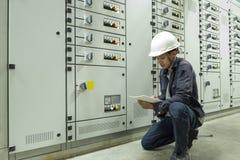 Os eletricistas est?o verificando os pain?is de controle el?tricos em plantas industriais imagens de stock royalty free