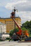 Os eletricistas na cubeta na altura reparam um revérbero em Moscou Fotografia de Stock