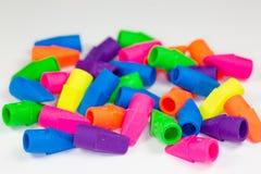 Os eliminadores de lápis coloridos desordenaram em uma superfície branca imagens de stock royalty free