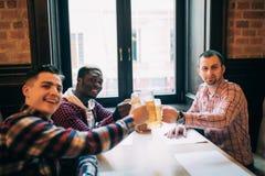 Os elogios consideráveis dos homens são de fala e de sorriso ao descansar no bar imagens de stock