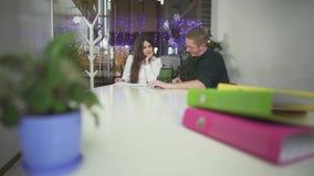 Os empregados discutem planos de negócios que estudam documentos com as estatísticas das vendas O chefe está explorando ofertas n filme