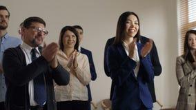 Os empregados diversos alegres dão boas-vindas ao gerente executivo video estoque