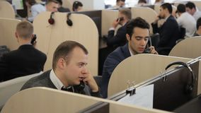 Os empregados do sexo masculino falam no telefone no centro de atendimento da empresa vídeos de arquivo