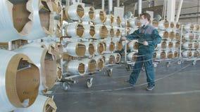 Os empregados nas máscaras monitoram bobinas da fibra de vidro que desenrolam para produzir materiais filme