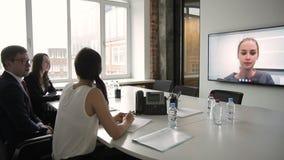 Os empregados novos assistem à conferência em linha no escritório moderno video estoque