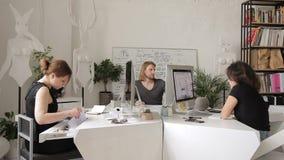 Os empregados trabalham no escritório criativo em seus desktops e computadores filme