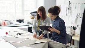 Os empresários atrativos do desenhista de roupa estão esboçando o entalhe com giz, trabalhando com tabuleta e fala Dia ocupado em vídeos de arquivo