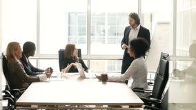 Os empresários diversos discutem a apresentação com o orador na reunião na sala de reuniões video estoque