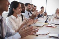 Os empresários em torno da tabela da sala de reuniões aplaudem a apresentação Fotografia de Stock