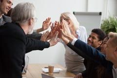 Os empresários novos e superiores multirraciais juntam-se às mãos que dão olá! Imagens de Stock Royalty Free