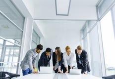 Os empresários novos estão no escritório e analisam o negócio com referência a imagens de stock royalty free