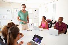 Os empresários que encontram-se no escritório de criam o negócio imagem de stock royalty free