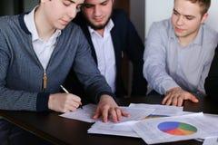 Os empresários sérios, novos equipam e a mulher desenvolve planos para o PR Imagens de Stock