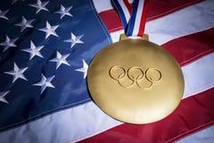 OS:en ringer guldmedaljamerikanska flaggan Arkivfoto