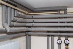 Os encanamentos nos calibres da isolação e de pressão fluem e retornam as tubulações na sala de caldeira de uma casa privada Imagem de Stock