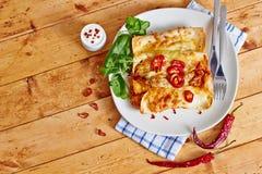 Os Enchiladas tornam côncavos com o pimentão encarnado com creme de leite Imagens de Stock Royalty Free