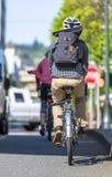 Os entusiastas dos ciclistas montam bicicletas ao longo da borda da estrada com tráfego ativo durante horas máximas fotos de stock royalty free