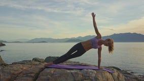Os equilíbrios magros da menina no braço esquerdo na ioga levantam na rocha video estoque