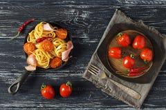 Os espaguetes aninham-se com presunto e tomates em uma frigideira, tomates de cereja em uma placa de madeira, fundo rústico escur Fotos de Stock