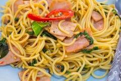 os espaguetes com bacon, a salsicha e manjericão friáveis fritados saem, alimento quentes e picantes, culinária internacional Fotografia de Stock