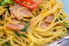 os espaguetes com bacon, a salsicha e manjericão friáveis fritados saem, alimento quentes e picantes, culinária internacional Imagem de Stock Royalty Free