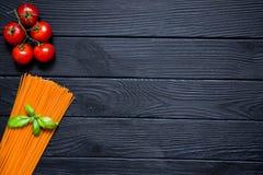Os espaguetes orgânicos do tomate com cerejas frescas e a manjericão folheiam em b Fotos de Stock