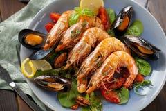 Os espetos assam camarões grelhados com ingredientes picantes alho e tomate prontos para servir fotografia de stock